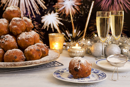 Oliebollen, traditional Dutch pastry for New Years Eve. With champagne and fireworks in the background. Stock Photo