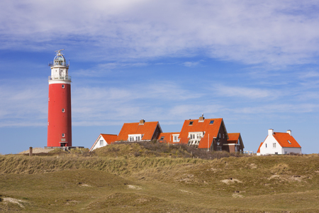 texel: The lighthouse of the island of Texel in The Netherlands on a sunny day. Photographed from across the dunes.