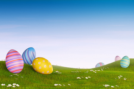 Decorated Easter eggs lying in the grass in a hilly landscape. Archivio Fotografico