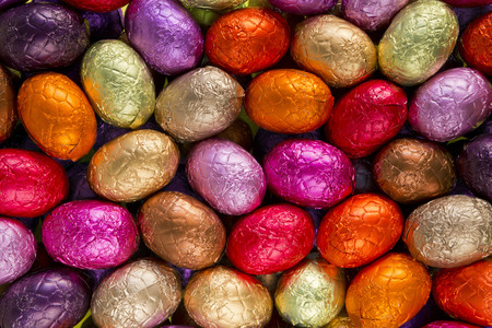 Assortment of red, yellow and pink chocolate Easter eggs. Standard-Bild