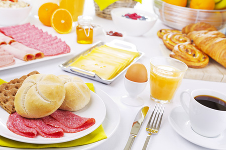 A large buffet-style continental breakfast on a brightly lit table.