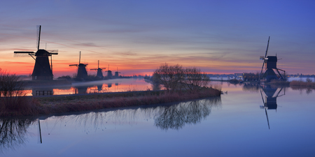 holland: Traditional Dutch windmills with ground fog just before sunrise. Photographed at the famous Kinderdijk. Stock Photo