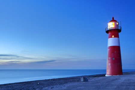 A red and white lighthouse at sea. Photographed at dusk near Westkapelle in Zeeland, The Netherlands. Stock Photo