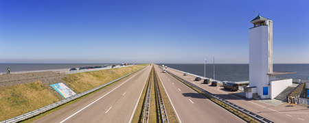 Traffic on the Afsluitdijk on a sunny day in The Netherlands. The Afsluitdijk is a dike over 32km damming off the former Zuiderzee, a salt water inlet of the North Sea. The monumental tower by architect Dudok marks the spot where the dike was closed in 19