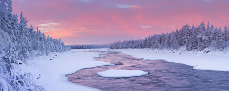 A rapid in a river in a wintry landscape. Photographed at the ijkoski rapids in the river in Finnish Lapland Muonionjoki at sunrise. Reklamní fotografie - 50741285