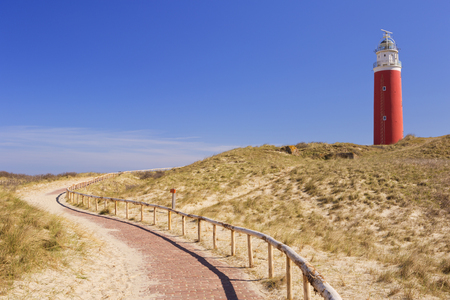 A footpath leading towards the lighthouse of the island of Texel in The Netherlands on a sunny day. Reklamní fotografie - 50850052