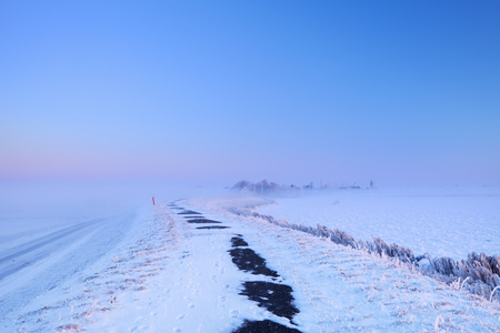 dike: Sunrise over a dike along a frozen lake on a record-breaking cold morning near Uitdam in The Netherlands. Stock Photo