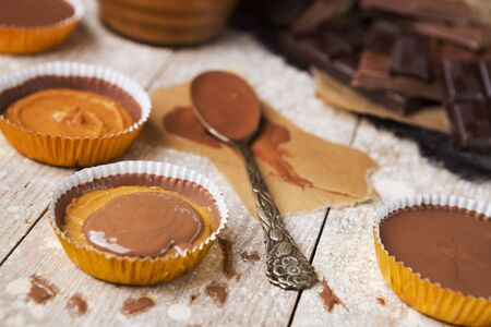 medium group of objects: Homemade peanut butter cups on a rustic wooden table. Stock Photo