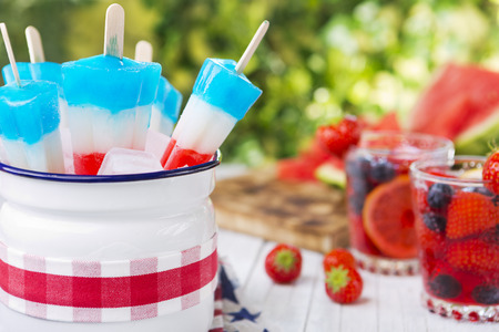 Homemade red-white-and-blue popsicles on an outdoor table with refreshing lemonade in the background. Imagens