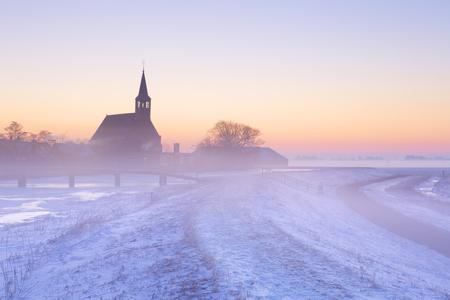 Una chiesa in un paesaggio invernale ghiacciato nei Paesi Bassi. Fotografato al sorgere del sole in una bella mattina di nebbia.