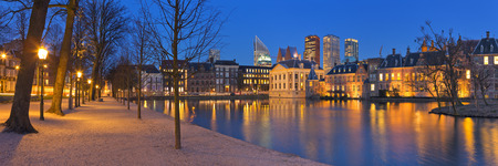 The Dutch Parliament buildings at the Binnenhof from across the Hofvijver pond in The Hague, The Netherlands at night.