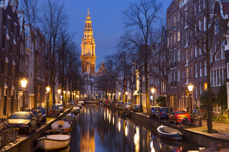 people in church: A church tower at the end of a canal in the city of Amsterdam, The Netherlands at night.
