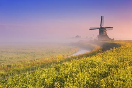 Een traditionele Nederlandse windmolen bij zonsopgang op een mooie mistige ochtend. Stockfoto