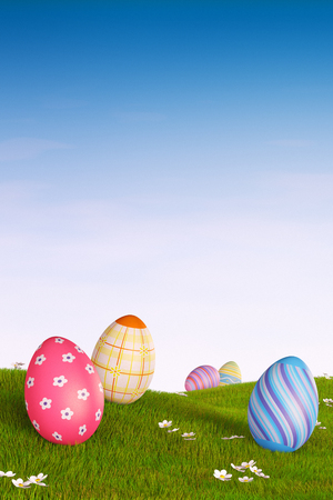 Decorated Easter eggs lying in the grass in a hilly landscape. Reklamní fotografie - 52740804