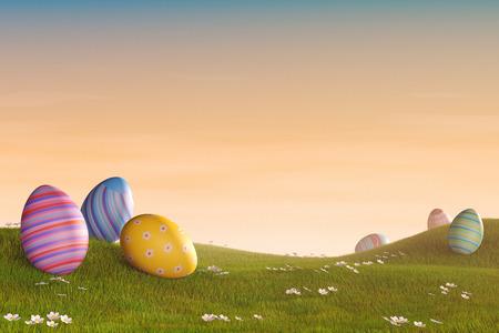 oeufs de Pâques décorés couchés dans l'herbe dans un paysage vallonné au coucher du soleil.