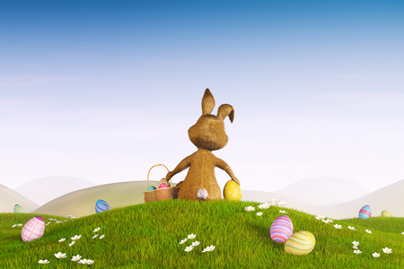 facing away: A cute Easter bunny sitting on a hill surrounded by easter eggs.