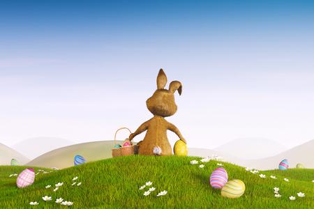 Een leuk Easter bunny zittend op een heuvel omringd door paaseieren. Stockfoto