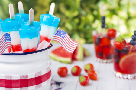 Homemade red-white-and-blue popsicles on an outdoor table with refreshing lemonade in the background. 스톡 콘텐츠