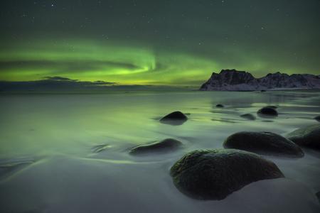 L'aurore boréale sur la plage Uttakleiv sur les Lofoten dans le nord de la Norvège en hiver.