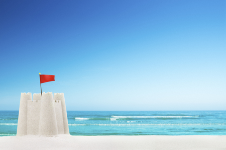 white sand: A sandcastle on a beautiful white sand beach in summer.