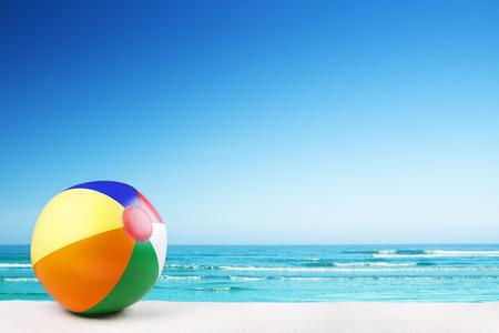 A beach ball on a beautiful white sand beach in summer.