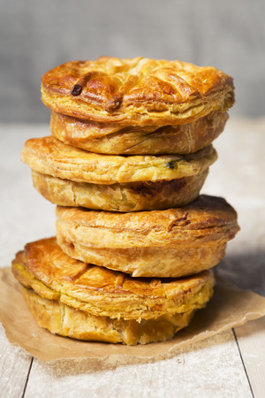 meat pie: A stack of homemade meat pies on a rustic table.
