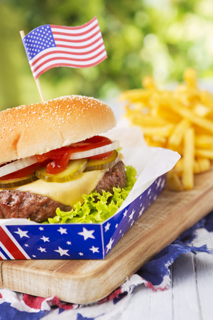 A tasty burger with fries on an outdoor table. Stock Photo