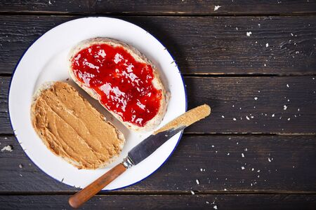 Peanut butter and jelly sandwich on a rustic table. Photographed from directly above.