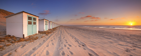 non urban scene: A row of beach huts on a beach on the island of Texel in The Netherlands. Photographed at sunset.