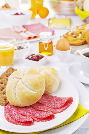 brightly: A large buffet-style continental breakfast on a brightly lit table.