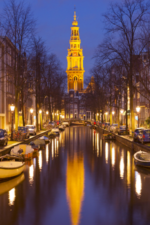 dutch culture: A church tower at the end of a canal in the city of Amsterdam, The Netherlands at night.