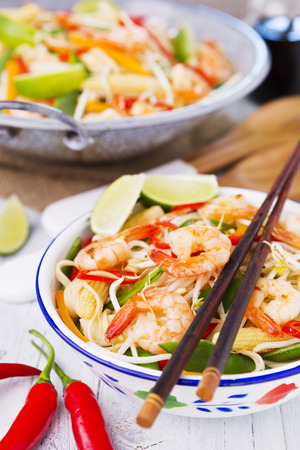 A healthy stir-fry of shrimp and vegetables served over noodles.