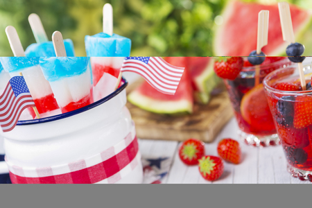 Homemade red-white-and-blue popsicles on an outdoor table with refreshing lemonade in the background.