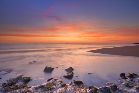 zeeland: A sandy beach with rocks in Zeeland, The Netherlands. Photographed at sunset.
