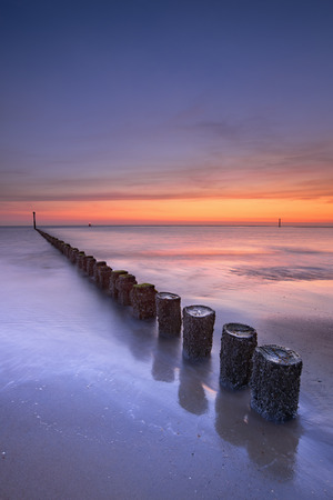zeeland: A breakwater on a sandy beach in Zeeland, The Netherlands. Photographed at sunset.