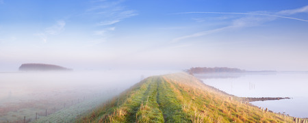 meer: A typical Dutch polder landscape with a dike along a lake. Photographed at the Veerse Meer in the province of Zeeland on a foggy morning. Stock Photo