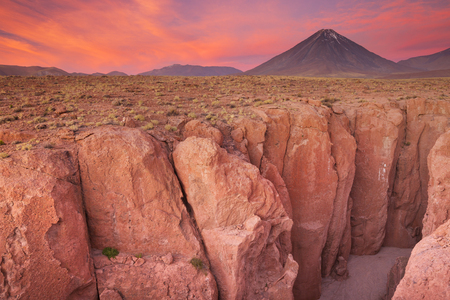 volcan: A narrow canyon with a volcano in the distance. Photographed at the foot of Volcan Licancabur in the Atacama Desert, northern Chile, at sunset.
