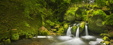 A stone bridge over a river with a small waterfall, near Mullerthal Luxembourg. Stockfoto