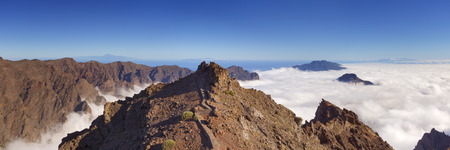 top angle: The mountains peaks around Roque de los Muchachos on La Palma, Canary Islands, Spain above the clouds. Stock Photo