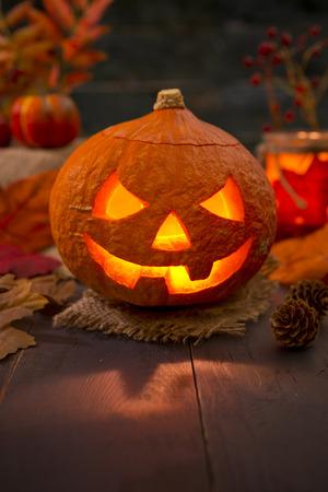 jack o lantern: Burning Jack OLantern on a rustic table with autumn decorations, darkly lit. Stock Photo