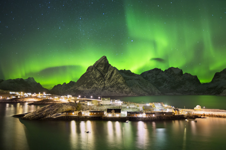 Panorama of the aurora borealis over the village of Reine on the Lofoten in northern Norway in winter. Stock Photo