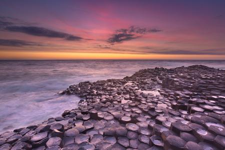 Coucher de soleil sur les formations de basalte de la Chaussée des Géants sur la côte nord de l'Irlande du Nord. Banque d'images - 63750663