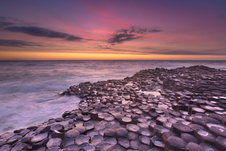 Sunset over the basalt rock formations of Giant's Causeway on the north coast of Northern Ireland. Stock Photo - 63750663