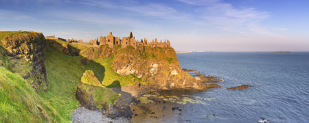 Early morning sunlight over Dunluce Castle at the Causeway Coast of Northern Ireland. Stock Photo