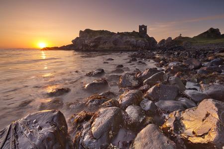 Sunrise at Kinbane Head with the ruins of Kinbane Castle on the Causeway Coast in Northern Ireland.