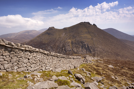 mourne: The Mourne Wall and the peak of Slieve Bearnagh in the Mourne Mountains in Northern Ireland on a sunny day. Stock Photo