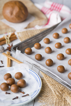 speculaas: A baking tray with unbaked pepernoten or kruidnoten, a Dutch delicacy for Dutch holiday Sinterklaas. Stock Photo
