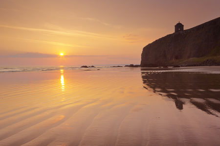 northern ireland: Sunrise over Downhill Beach and cliffs on the Causeway Coast in Northern Ireland.
