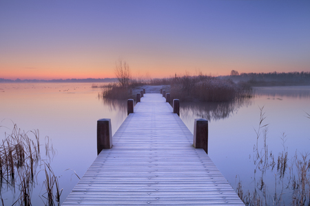 A quiet lake in The Netherlands with a boardwalk on an early morning.
