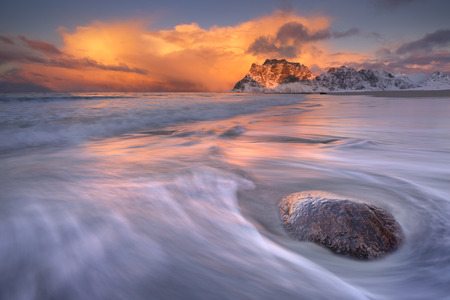 Spectacular light and a distant snow storm at beautiful Uttakleiv beach on the Lofoten in northern Norway.